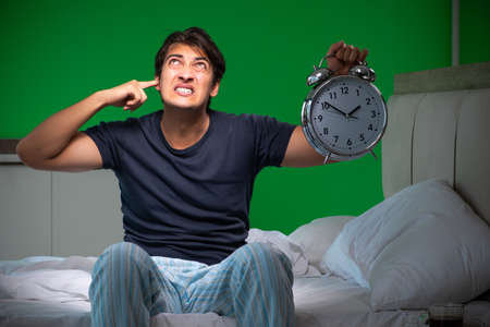 Young handsome man suffering from insomnia at home Imagens