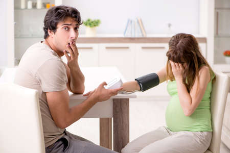 Husband checking pregnant wifes blood pressure Stok Fotoğraf