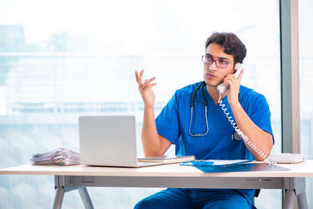 Young handsome doctor working in the hospital Stock Photo
