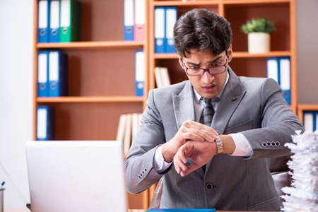 Young handsome businessman unhappy with excessive work