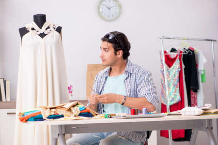 Young handsome tailor working in his workshop Stock Photo