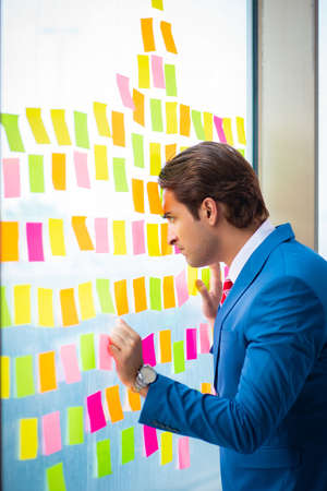 Young handsome employee with many conflicting priorities Stock Photo