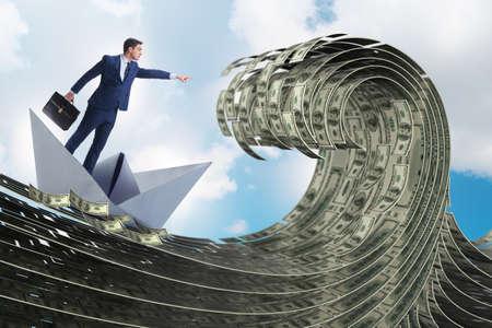 Businessman riding paper boat in dollar sea Banco de Imagens