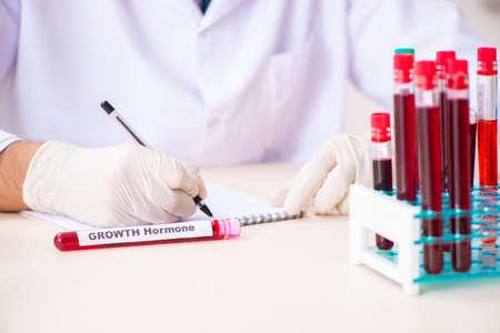 Asistente de laboratorio guapo joven probando muestras de sangre en el hospital Foto de archivo
