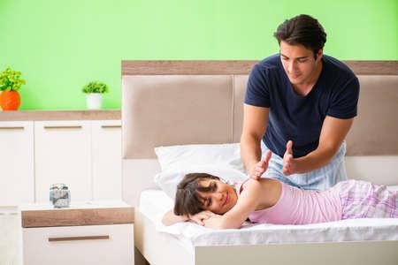 Hombre haciendo masaje a su esposa en el dormitorio Foto de archivo