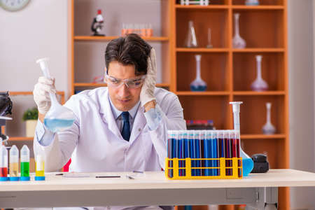 Young handsome biochemist working in the lab Stock Photo