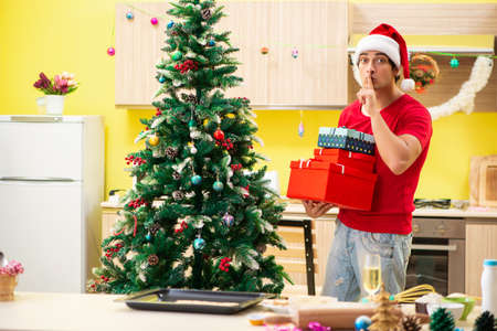 Young man celebrating Christmas in kitchen