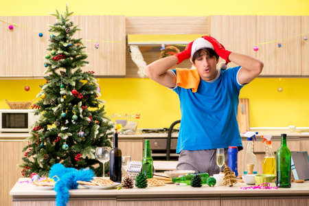 Young man cleaning kitchen after Christmas party Stock Photo - 112664658