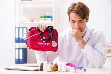Young doctor with first aid kit in hospital Standard-Bild