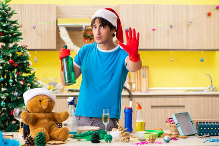 Young man cleaning kitchen after Christmas party Stock Photo