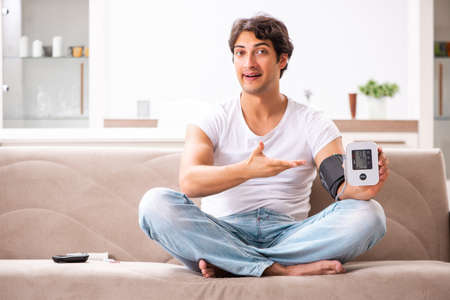 Young man measuring blood pressure at home