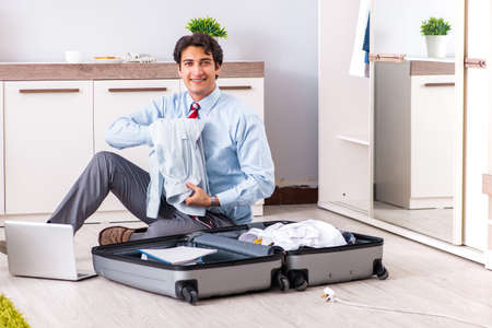 Young handsome businessman preparing for trip Stock Photo