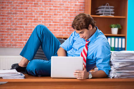 Young employee with excessive work sitting at the office