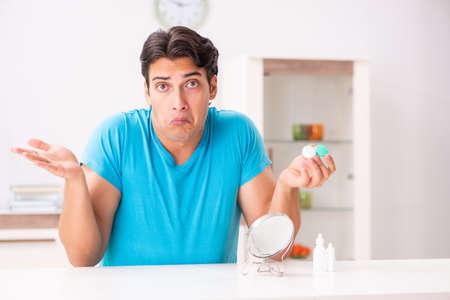 Mann versucht Kontaktlinsen zu Hause