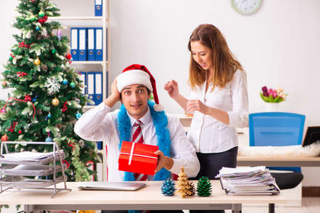 Colleagues exchaing christmas presents in office