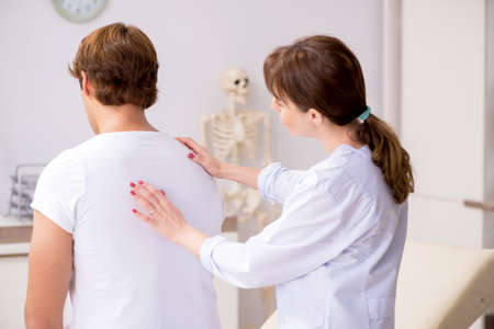Male patient visiting young female doctor chiropractor Stock Photo