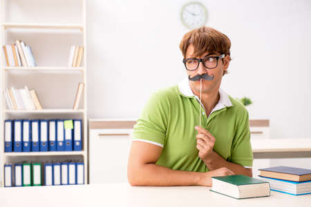 Student with fake moustache reading book Stock Photo