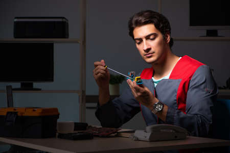 Young handsome repairman repairing computer
