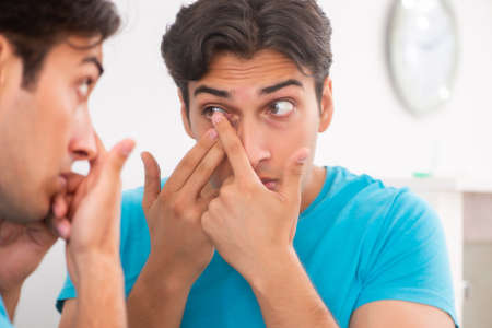 Man trying contact lenses at home Archivio Fotografico