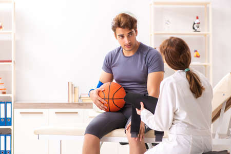 Handsome basketball player visiting female doctor traumatologist Stock Photo