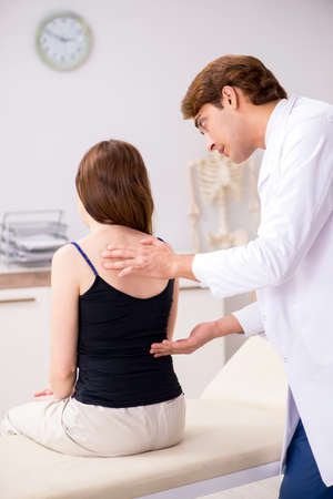 Female patient visiting young handsome doctor chiropractor