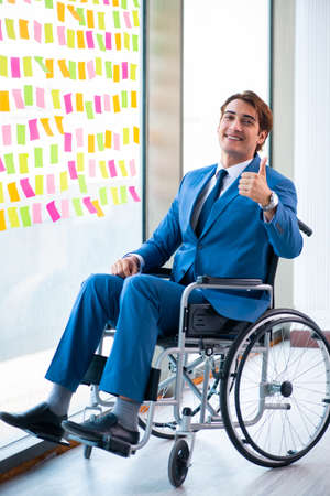 Young handsome man in wheelchair with many conflicting prioritie Imagens