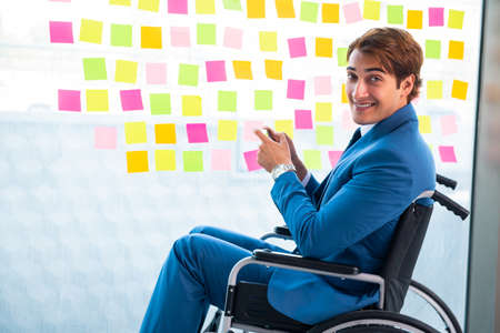 Young handsome man in wheelchair with many conflicting prioritie Banque d'images