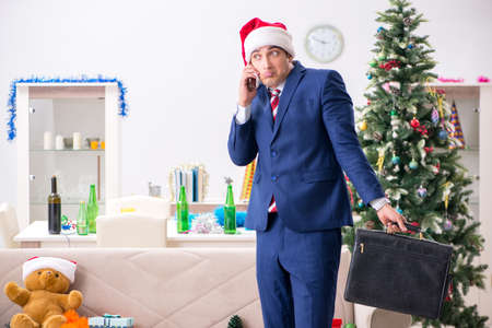 Young handsome employee celebrating Christmas at workplace Stock fotó