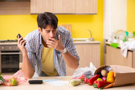 Young man calculating expences for vegetables in kitchen Imagens