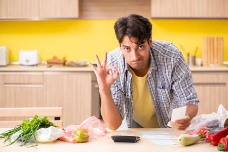 Young man calculating expences for vegetables in kitchen Stock Photo