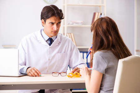 Young woman visiting male doctor ophthalmologist in hospital