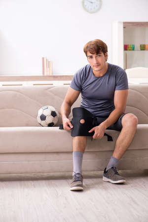 Injured man recovering at home from sports injury Stock Photo - 113840112
