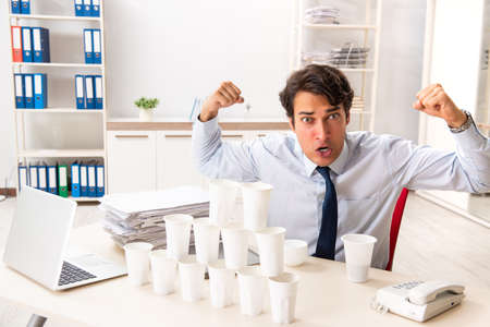 Young employee building pyramid from plastic cups