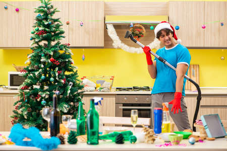 Young man cleaning kitchen after Christmas party Banque d'images