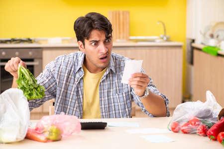 부엌에서 야채 비용을 계산하는 젊은 남자