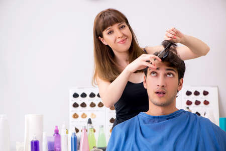 Young attracrive man visiting female barber