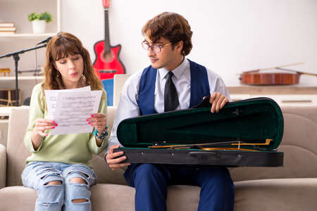 Young woman during music lesson with male teacher