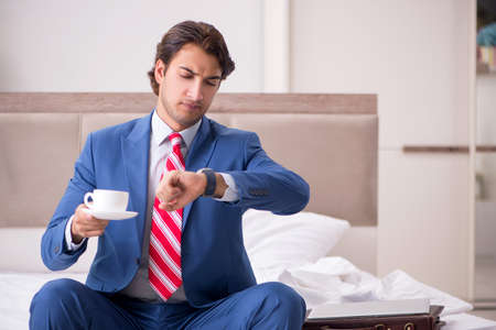 Young employee working at home sitting on the bed