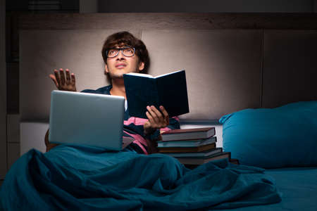 Young student preparing for exams at night at home Stock Photo