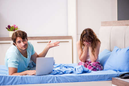 Young couple with laptop in the bedroom