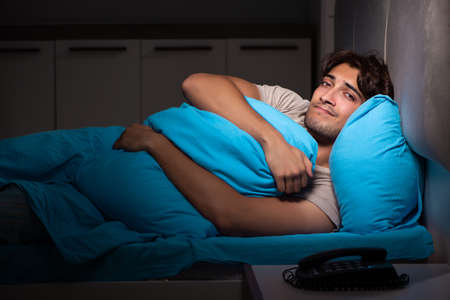 Young handsome man suffering from insomnia in bed