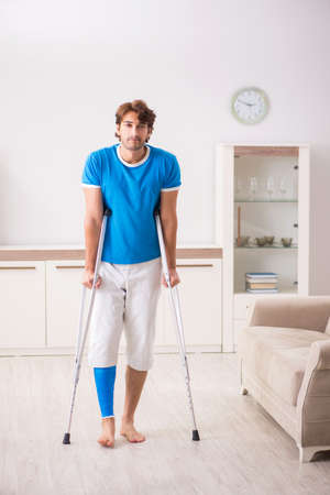 Leg injured young man with crutches at home