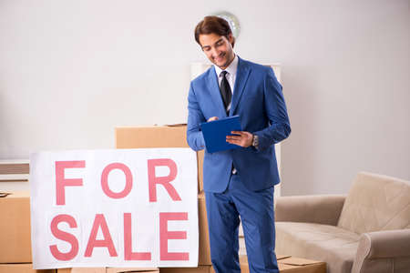 Young handsome realtor selling flat Foto de archivo