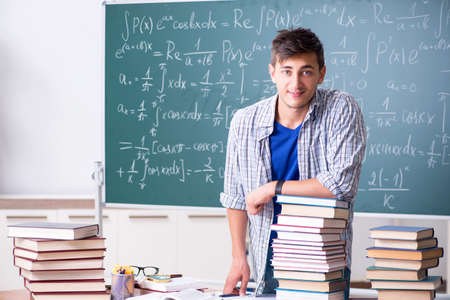 Young male student studying math at school