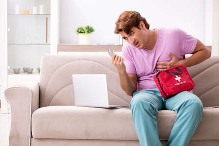Sick man at home with first aid kit