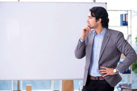 Young handsome teacher in front of whiteboard