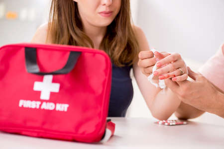 Young family getting treatment with first aid kit 版權商用圖片