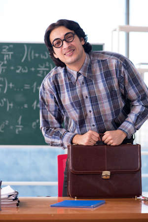 Young funny math teacher in front of chalkboard Foto de archivo