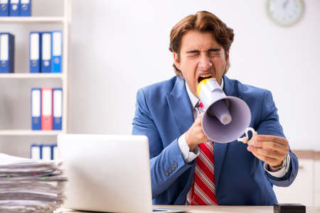 Deaf employee using hearing aid in office Stock Photo