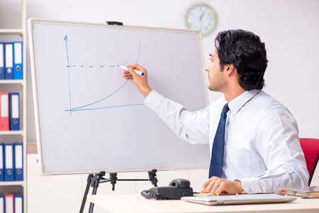 Young handsome financial speciaist in front of white board